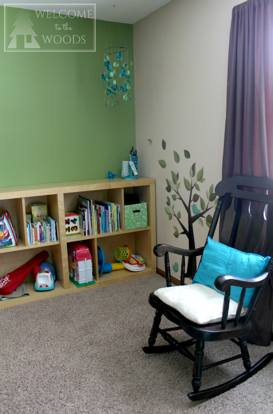 Rocking chair and bookshelf in a room designed for small child.