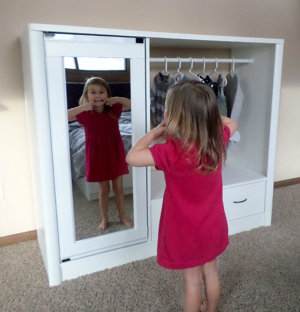 Little girl making silly face in mirror