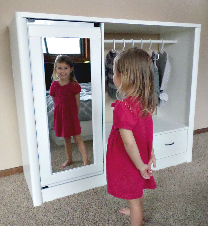Little girl smiling at self in mirror