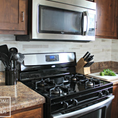 Beautiful stainless steel appliances and fake marble tile backsplash in this kitchen makeover.