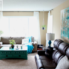 Beautiful modern eclectic living room design with mismatched couches, huge abstract artwork, bright teal accents, painted furniture, and ethereal white curtains.