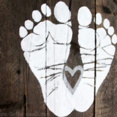 See this adorable baby shower gift idea with footprints painted on a pallet wood sign.