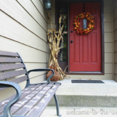 "Front entrance fall decor, wood bench with ""Hello"" sign, leaf wreath, corn stalks, and gourds."