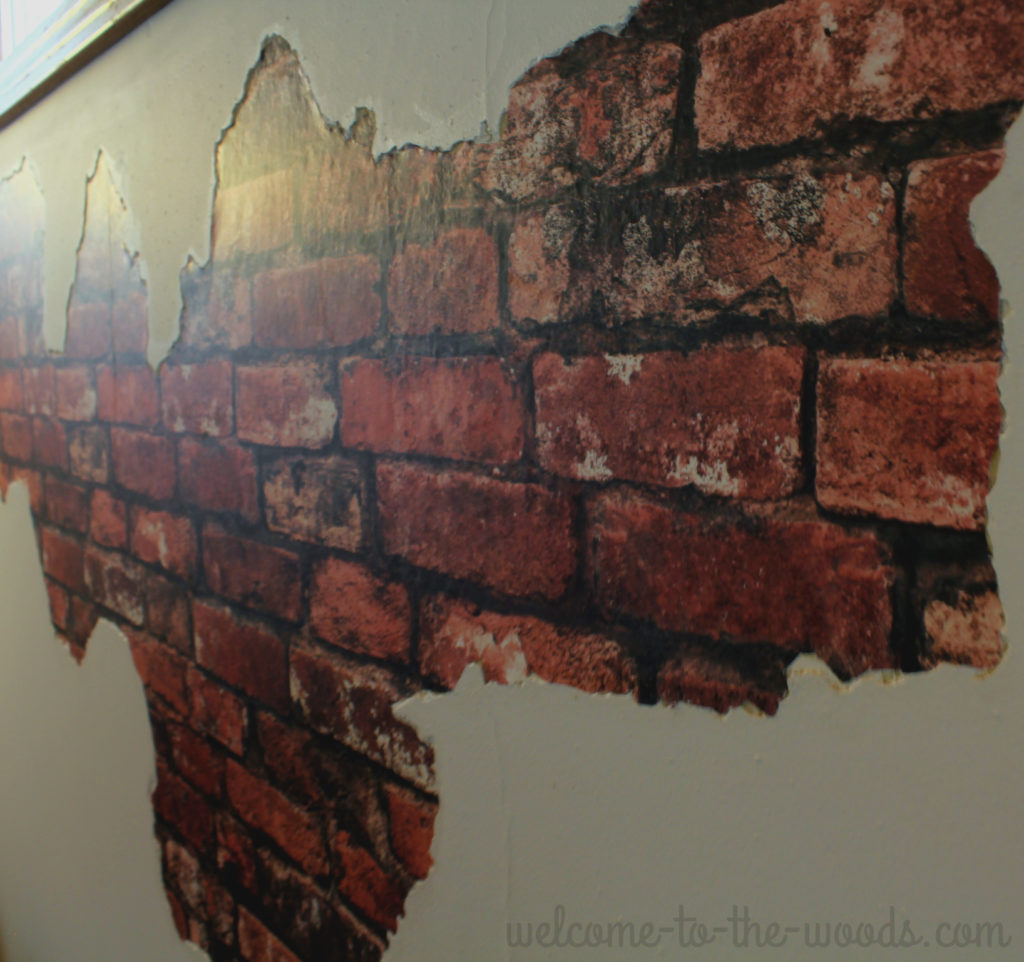 The edge of the plaster chipped off matches right up to the faux brick wall paper giving the finish a realistic look.