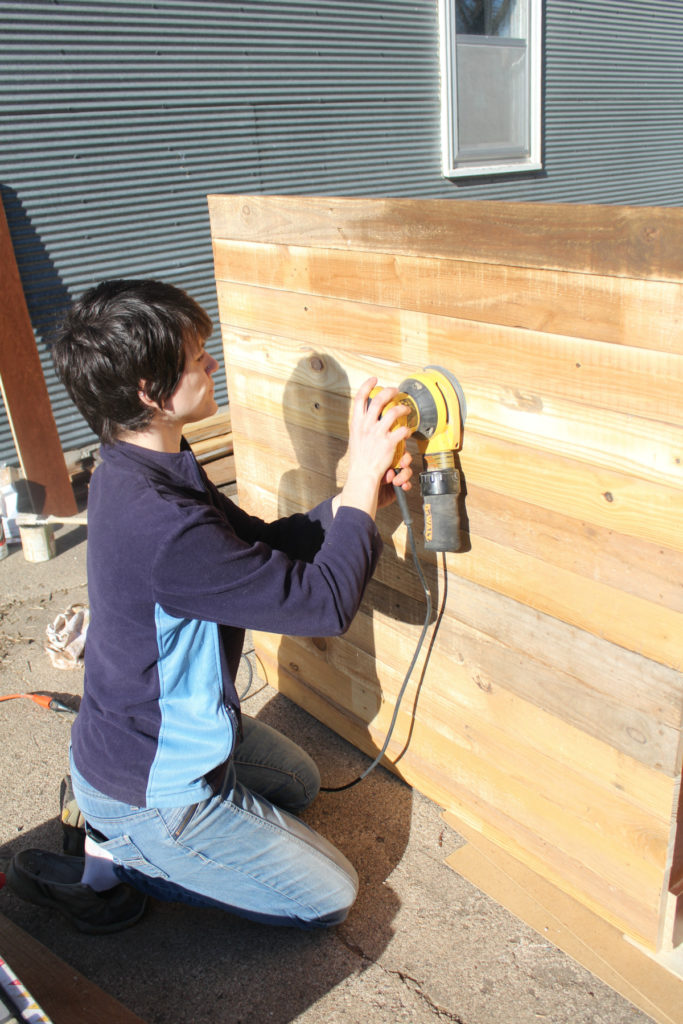 Sanding down reclaimed wood to stain it.