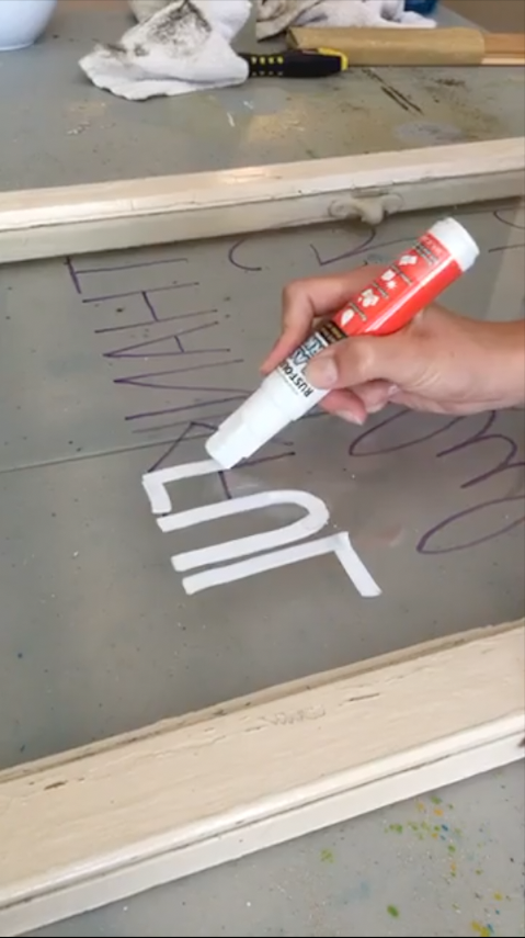 Write on glass with a temporary window marker to decorate old window pane