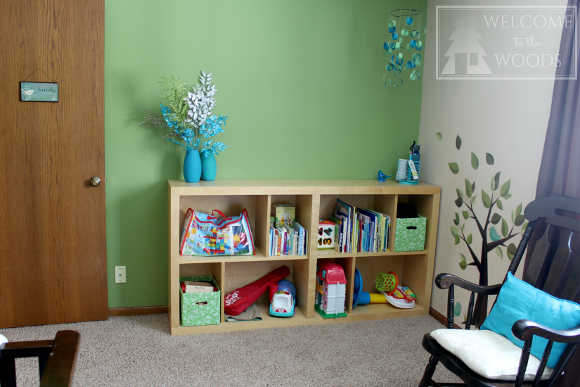 Nursery furniture placement of shelves & rocking chair, changing table & crib.