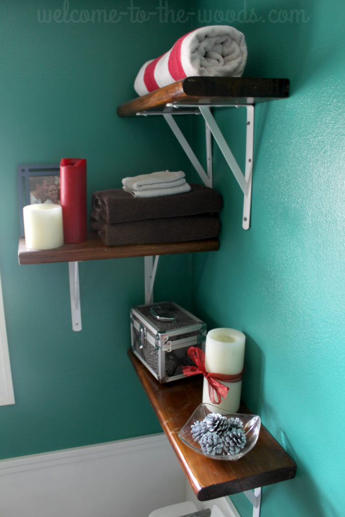 Decorations for Christmas on the shelves. Candles, pine cones, and rolled towels.