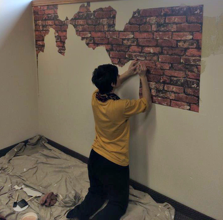 Applying brick faux wallpaper to plaster wall for an old world faux finish.