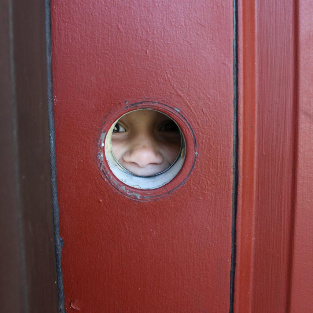 Playing peekaboo through the door hole