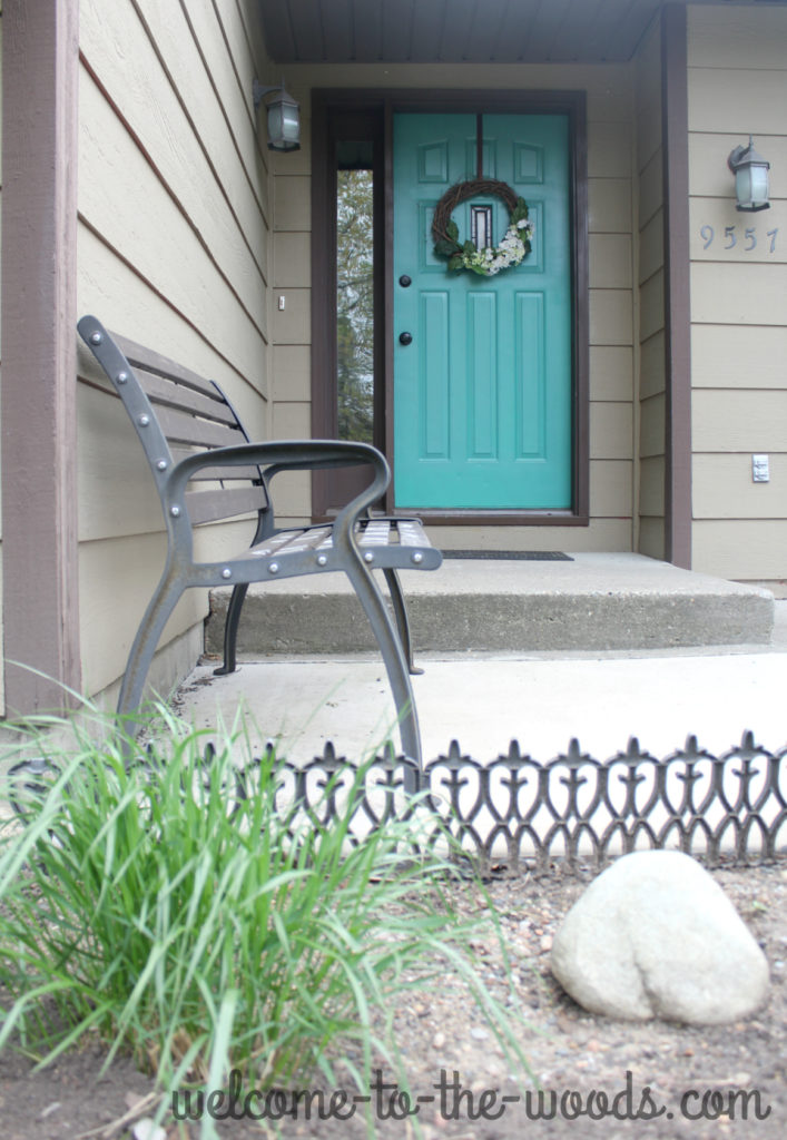 Beautiful front entry to bilevel, split foyer house. Bench and bright teal front door make it inviting!