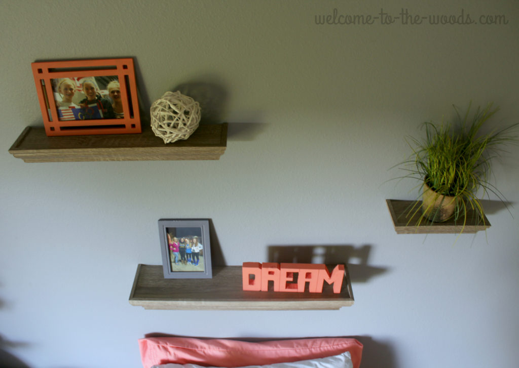 Shelving arrangement above bed in teenage girls bedroom design