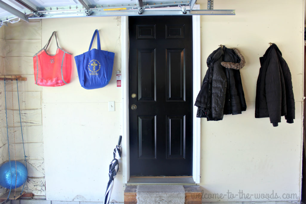 Painting your garage entrance door black will prevent dirt and grime from showing as quickly. See all the functional tips in this garage entrance redo