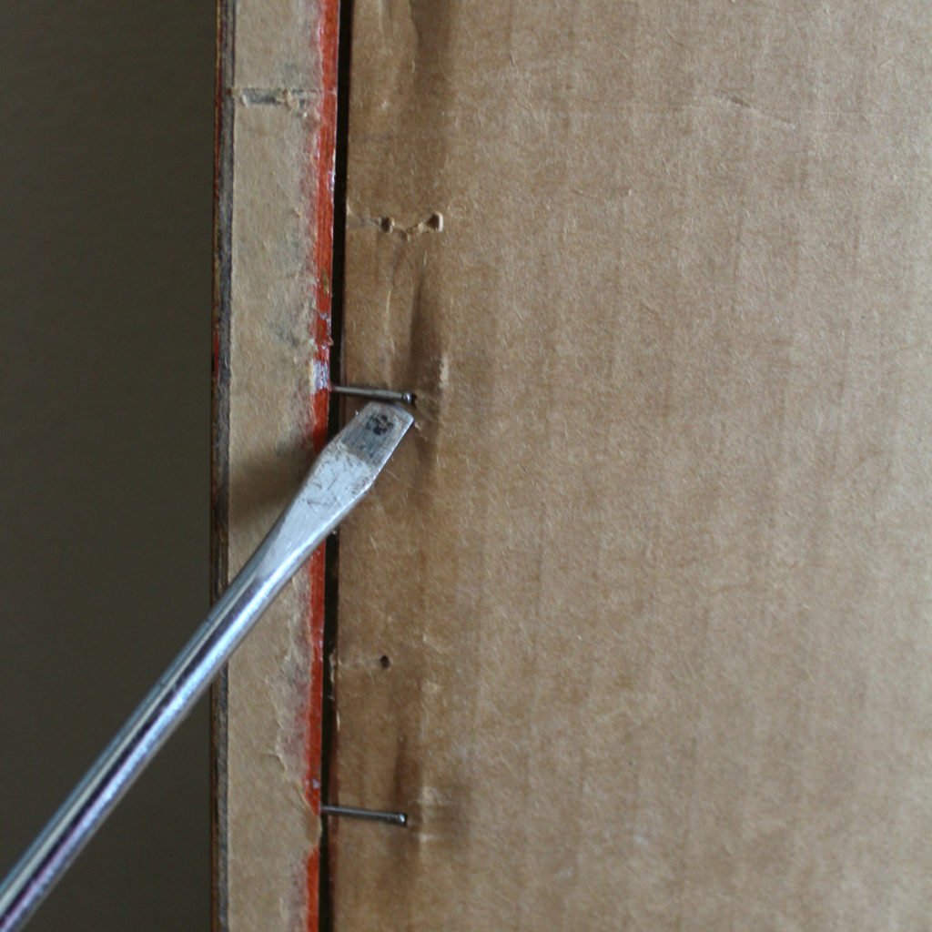 Use a screw driver to remove nails or staples that hold in the photo frame's contents, usually cardboard backing.