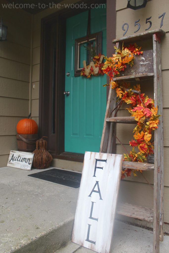 Front step porch or entrance fall decor idea. I love the old ladder and distressed wood autumn signs!
