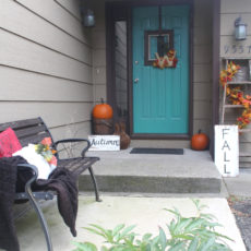Beautiful fall front door entrance decor! Vintage items like the wood ladder and bucket as well as traditional orange colors in the leaves and pumpkins make it look so welcoming and cozy! Especially with the teal door!