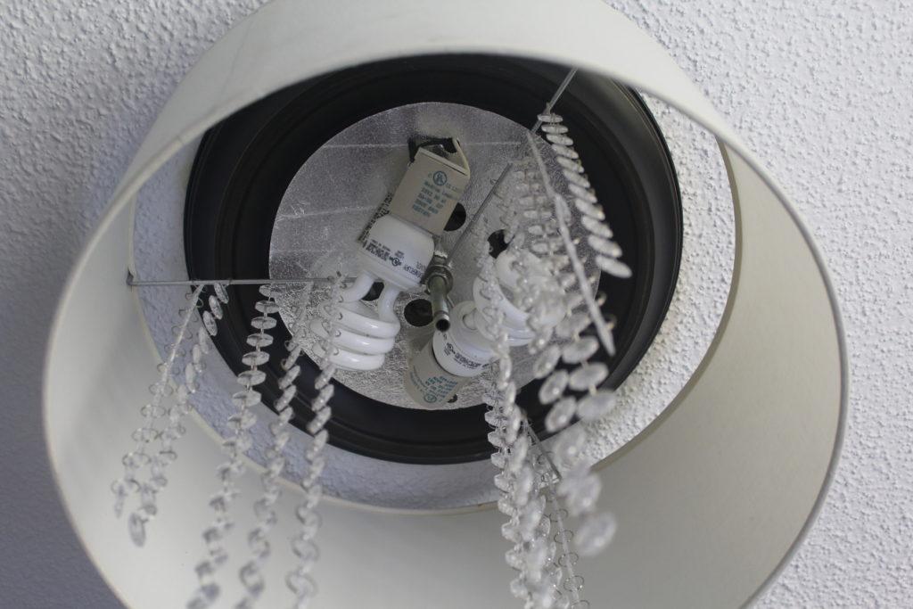 The inside of DIY drum chandelier, reattaching light bulbs