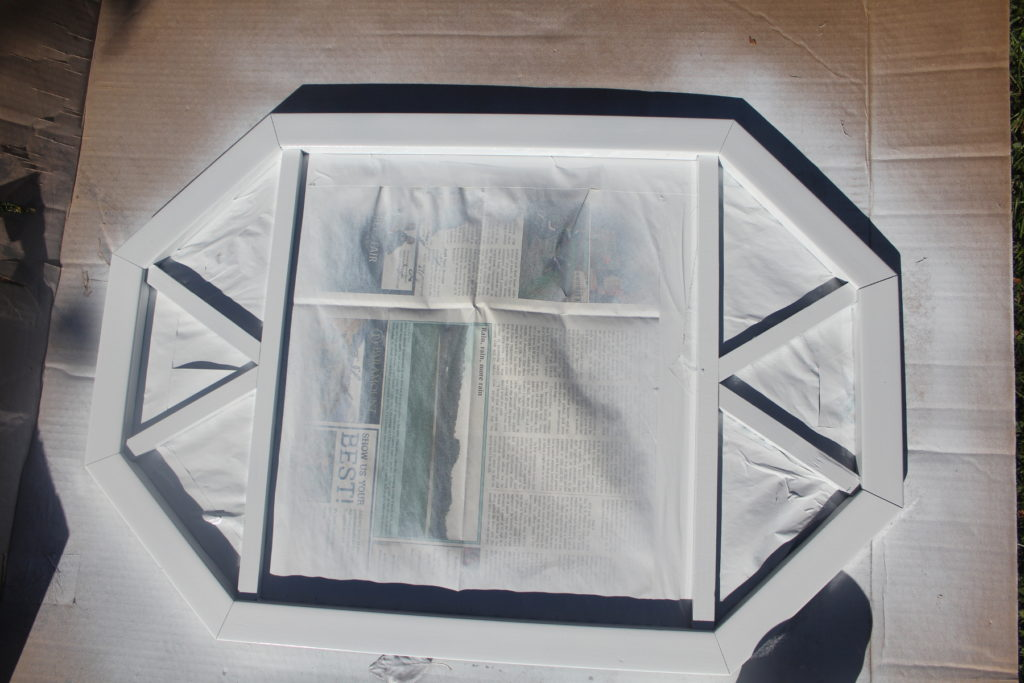 Spray painting mirror frame white using newspaper and frog tape