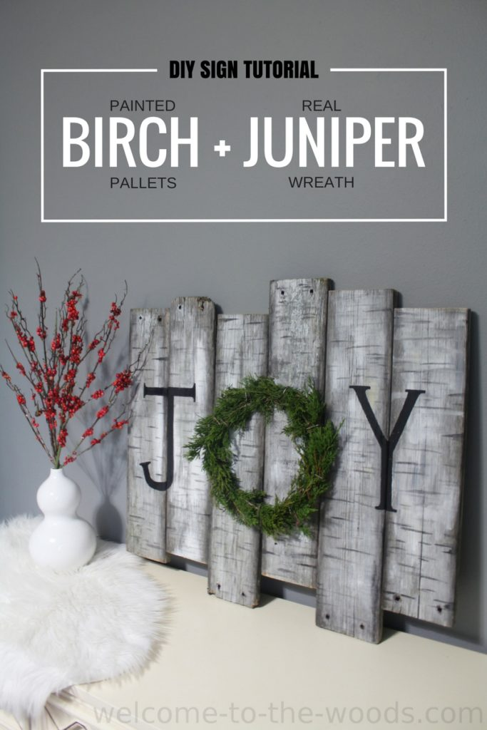 "A DIY wood sign tutorial for holiday decor to paint old dock board like birch trees and make a real juniper wreath to spell ""JOY""."
