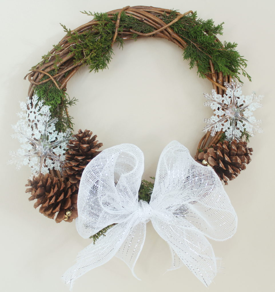 Gorgeous and simple white winter wreath with a big burlap bow, pine cones, snowflakes, and evergreen branches