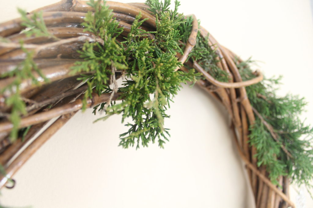 Weave evergreen clippings from outside between your grapevine wreath for seasonal style