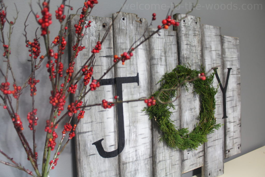 "Painted birch wood sign from old dock boards and a real juniper wreath make this adorable holiday decor that spells ""Joy"""