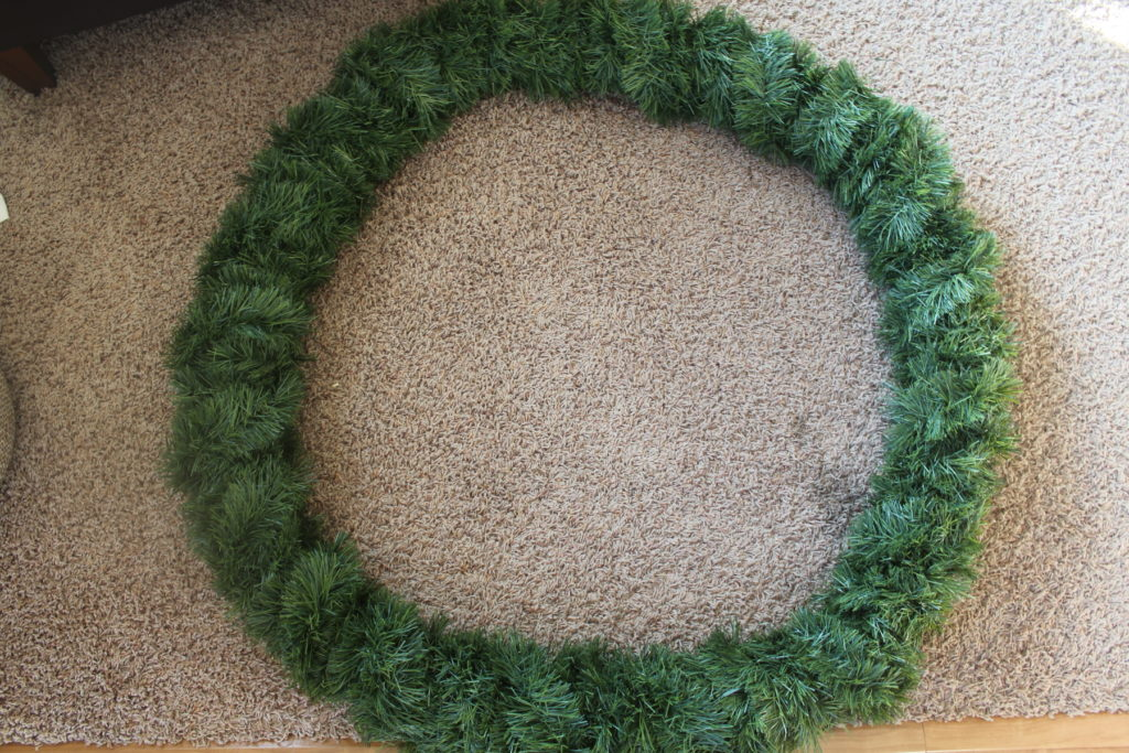 Wrap soft garland around pool noodles to make a VERY large evergreen wreath as Christmas decor