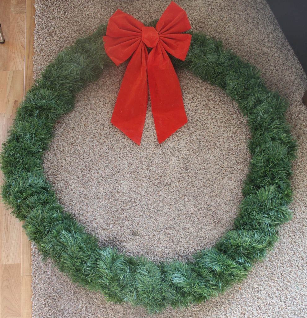 Large evergreen wreath with red bow for exterior home decor at Christmas time, photo prop, or anything!