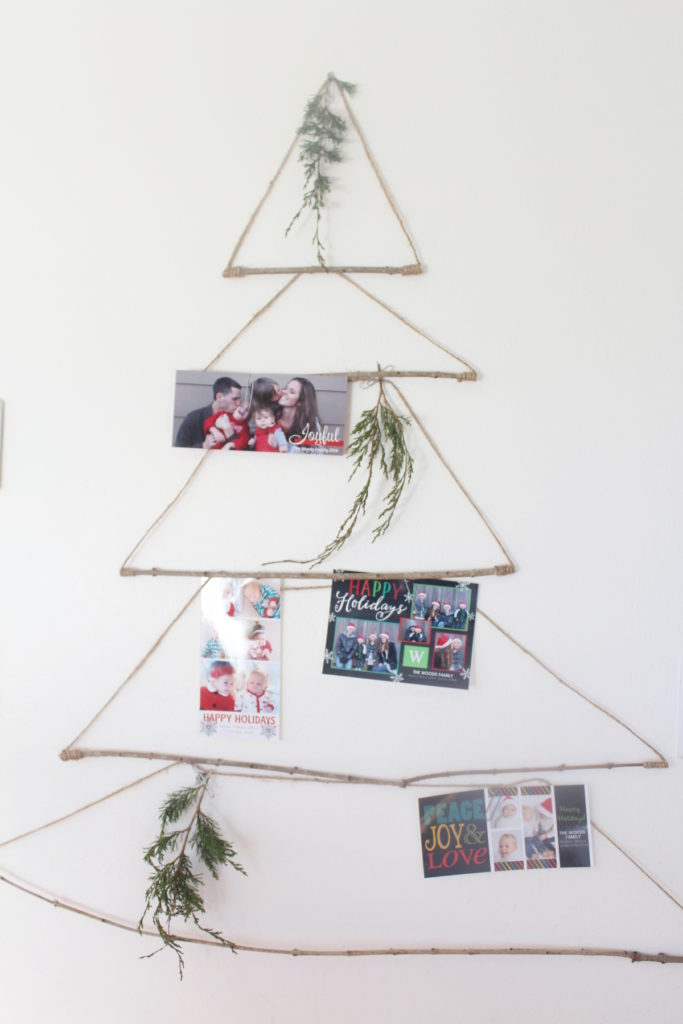 Make a Merry Mail Tree using sticks and twine hanging on the wall for displaying Christmas Cards