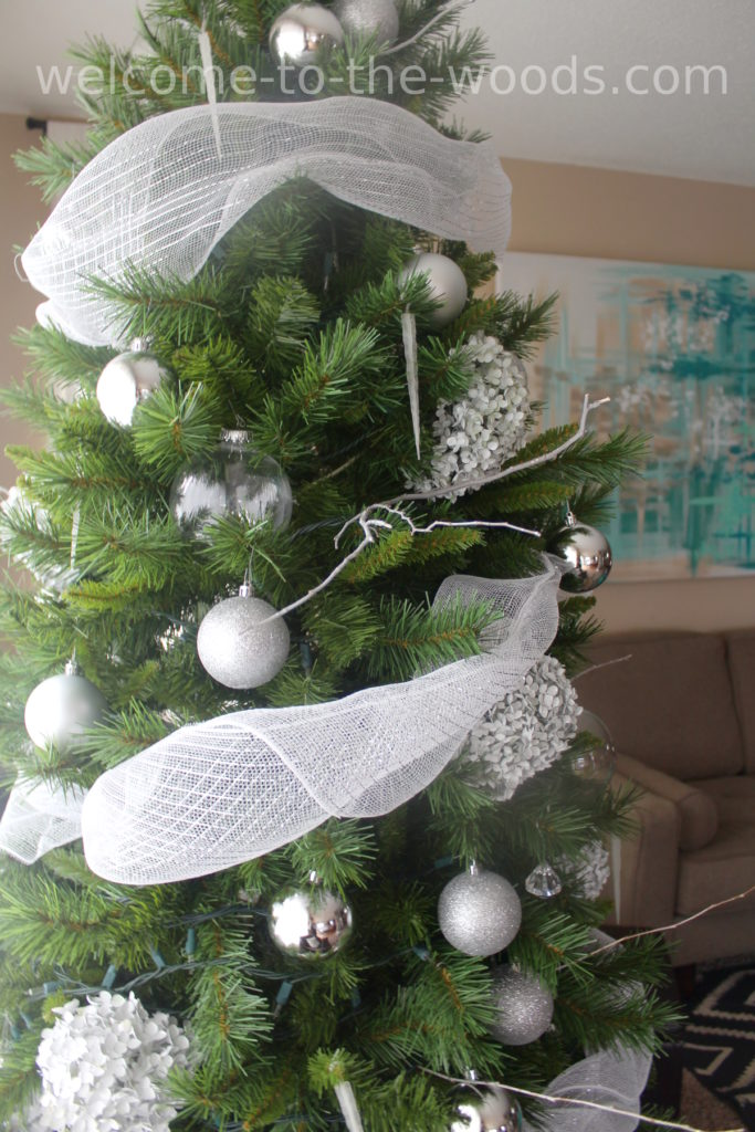 Close up of White Woodland Winter Christmas tree. Burlap ribbon, silver ornaments, painted hydrangea blooms, icicles, glittery branches and more!