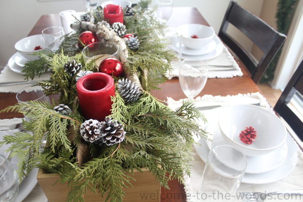 Christmas Tablescape with natural elements, evergreen, birch branch, pine cones, ornaments, candles, and more.