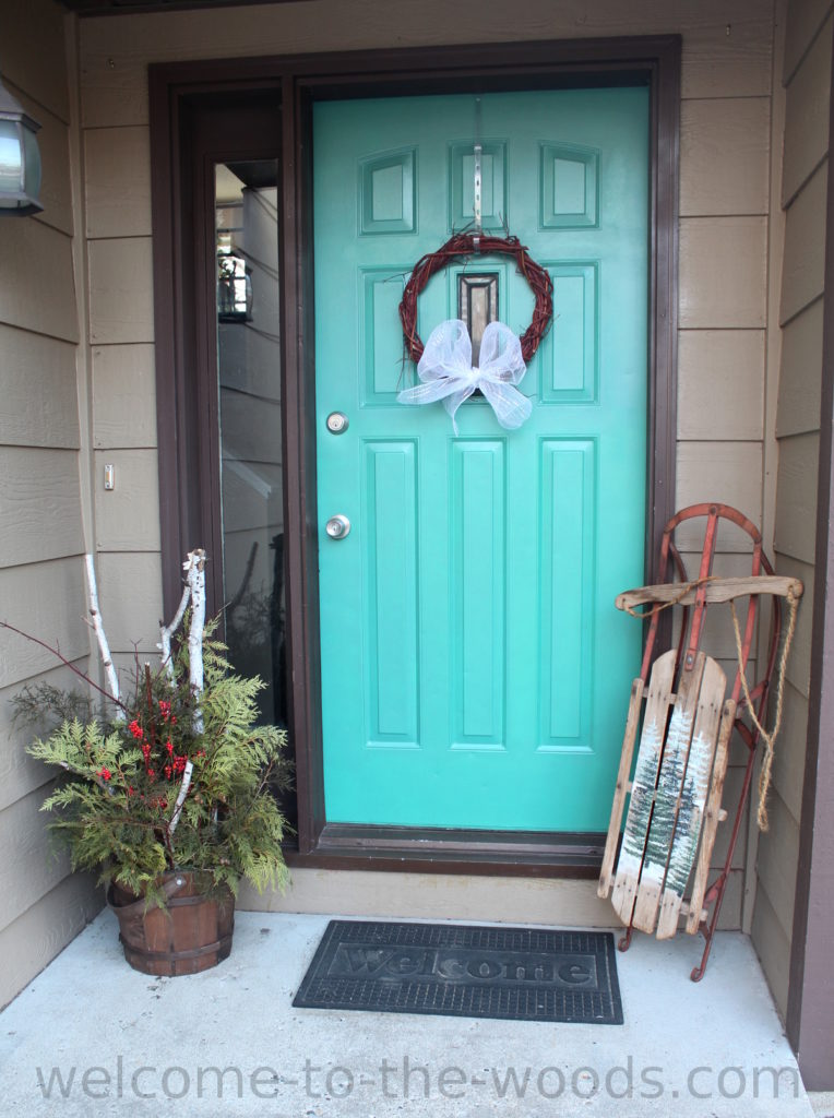 Love this simple entryway Christmas decor idea. Painted antique sled, birch wood and evergreen planter, red twig dogwood front door wreath.